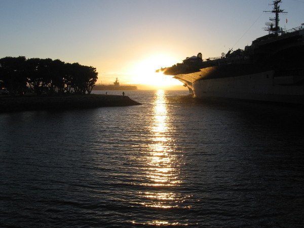 The sun nears the horizon beyond the USS Midway Museum, reflecting from tranquil San Diego Bay.