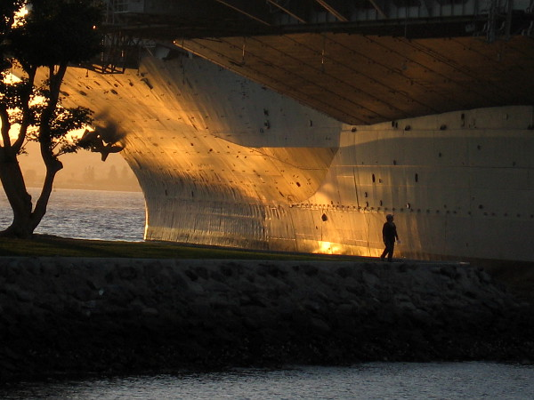 Late sunlight splashes the immense bow of the USS Midway with gold.
