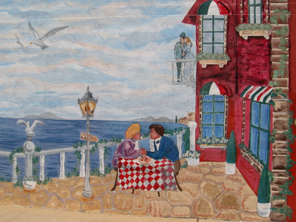 Lovers stand on a balcony, and eat Italian food by the ocean.