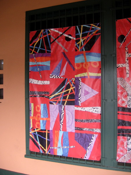 A banner showing a contemporary quilt outside Visions Art Museum at Liberty Station.