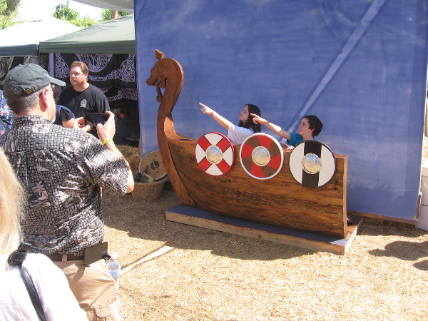 Kids pose in a Viking longship for a fun photo.