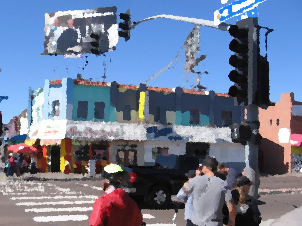 People wait to cross Mission Boulevard in Mission Beach.