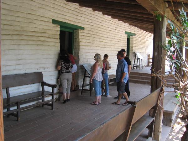Visitors to Old Town San Diego State Historic Park look into a restored room of La Casa de Estudillo.