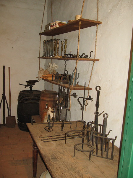 More shelves against one wall contain iron tools and basic furnishings like candlesticks for sale.