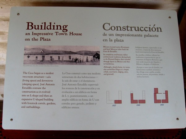 Sign describes how the casa started as a modest two-room structure and eventually grew into an expansive U-shaped building with a courtyard and outbuildings.