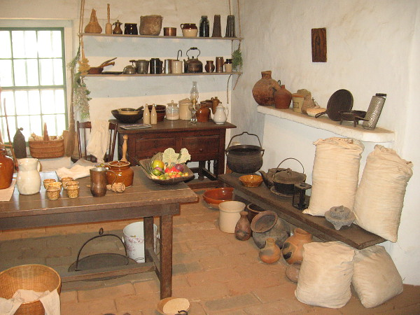 Jars, pots, sacks of flour and fruit are among the many items seen in the rather primitive kitchen.