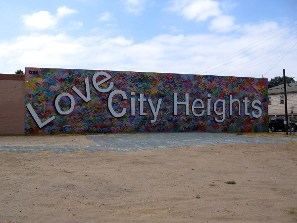 A large, welcoming Love City Heights mural greets people along University Avenue near Interstate 15.