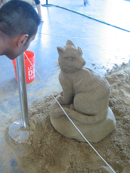 A visitor to the 2018 U. S. Sand Sculpting Challenge in San Diego admires a small work of art.