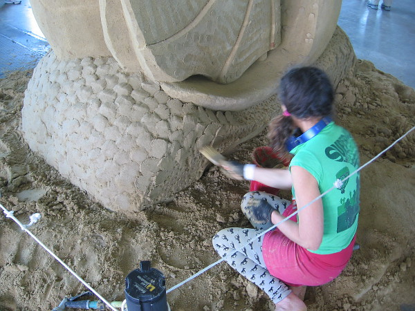 Meg Murray concentrates on her poetic sand art.