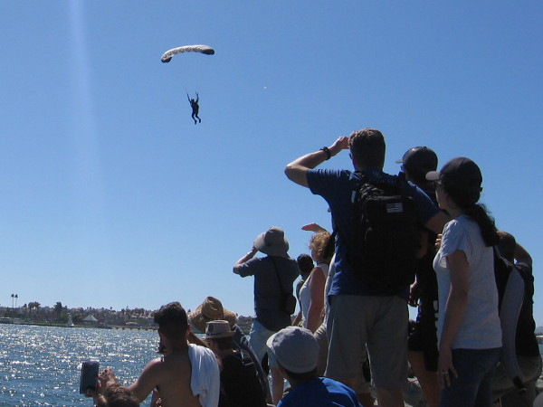 Here comes another contestant. Helicopters took parachutists high above the water, and the crowd shielded their eyes from the sun to see them descending.