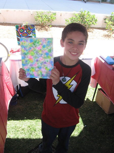 The smiling young man shows his super colorful artwork!