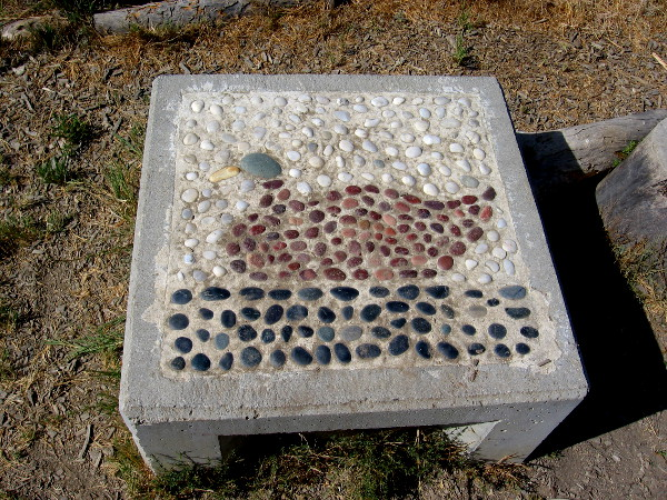 Several small concrete seats were decorated with colored stone mosaics. This one features a mallard duck.