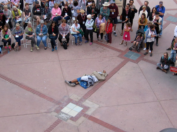 Audience looks down with expectation as a dancer portrays a homeless person during the first stage of 2018 Trolley Dances at Hazard Center.