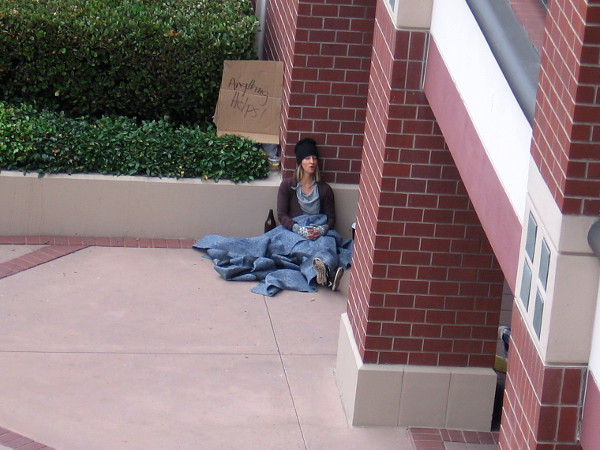 As the audience gathers on the south side of the Hazard Center shopping mall, one performer appears be homeless, sitting alone.