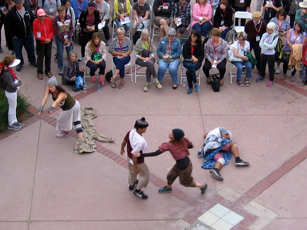 Dancers converge in front of the audience. The dance portrays different people who are homeless.