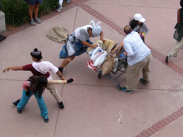 Performers tussle over the shopping cart, while a nearby couple dances.