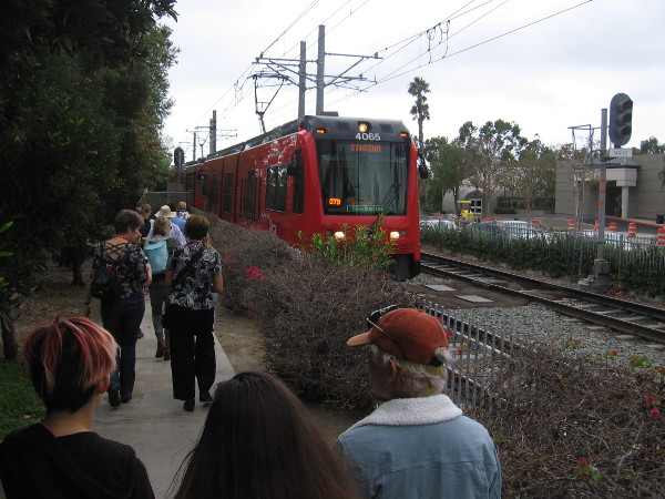 The audience heads west along the San Diego Trolley tracks.