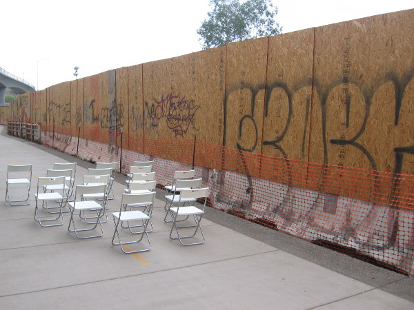 Empty chairs and graffiti on a construction wall await at the next Trolley Dance stage.