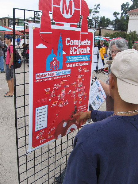 Visitors to Balboa Park look at a map showing the many exhibitors and demonstrations at 2018 Maker Faire San Diego.