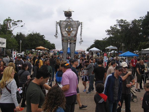 A big crowd surrounds 30-foot-tall, flame throwing Robot Resurrection during 2018 Maker Faire San Diego in Balboa Park.