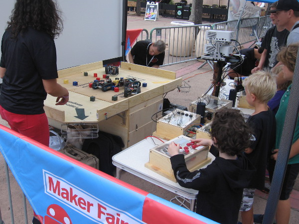 Other kids have fun controlling robots that move blocks.