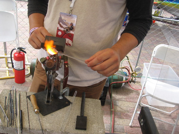 This guy was melting glass and forming a beautiful jewelry pendant.