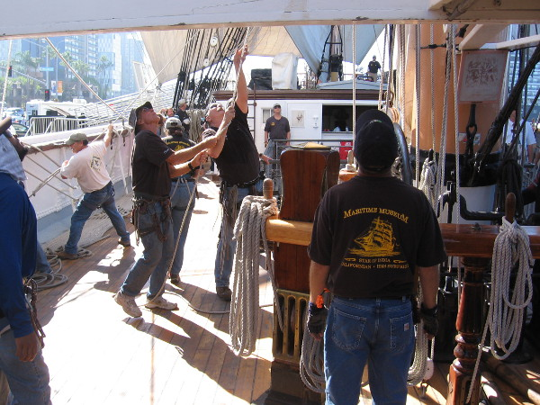 Pulling ropes to manipulate the yards and sails.