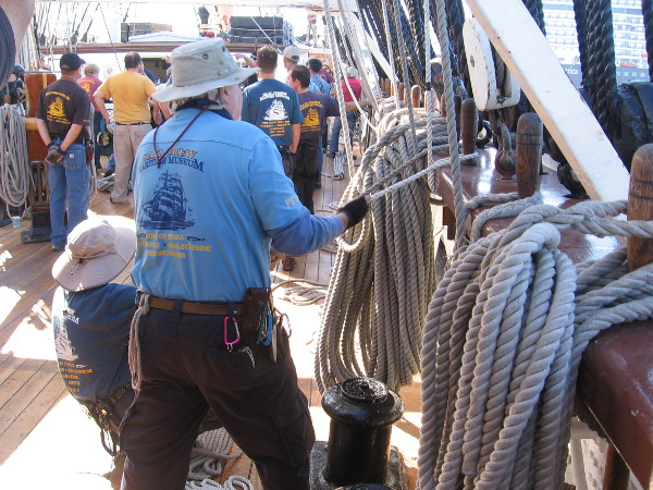 Securing one rope tightly to a belaying pin on the ship's wooden pinrail.