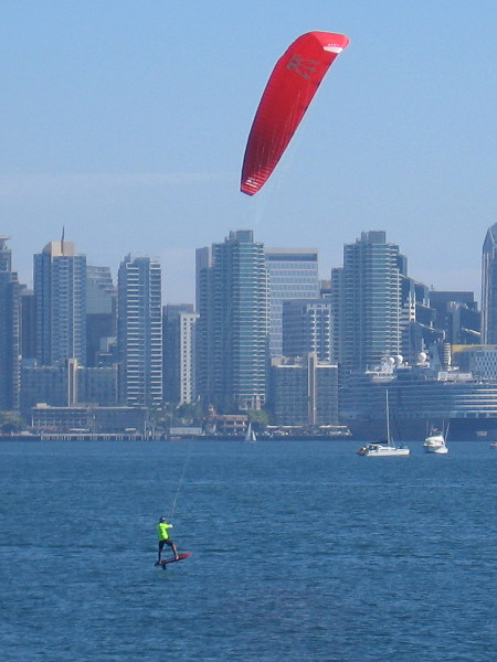 A highly skilled kite boarder flies above the blue water of San Diego Bay.
