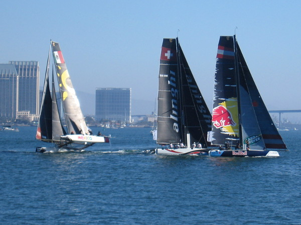 The race has begun! One catamaran tips upward in the wind, as its crew tries to obtain maximum speed.
