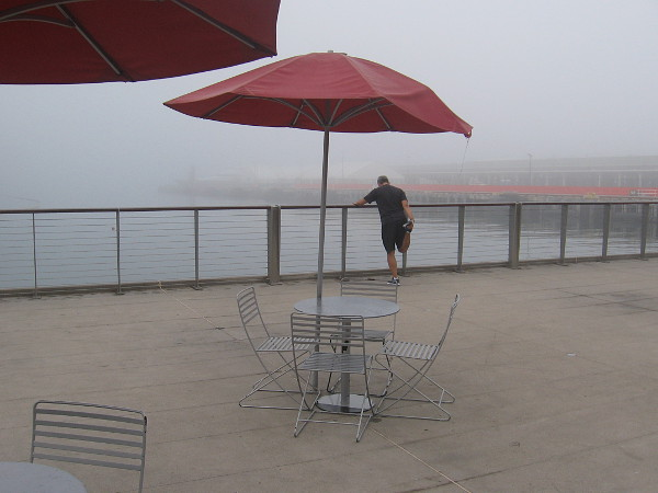 A jogger stretches on the observation platform near Broadway Pier, beside the fog covered water.