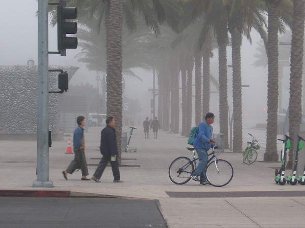 People head down the sidewalk in the early morning fog.