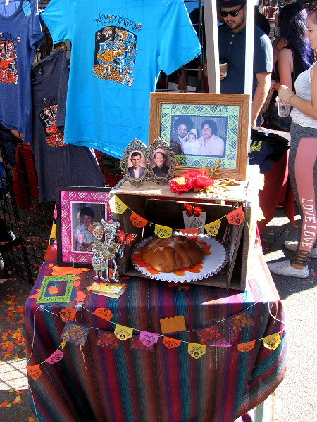Another small altar (or ofrenda) included photos of deceased loved ones, papel picado, and pan de muerto.