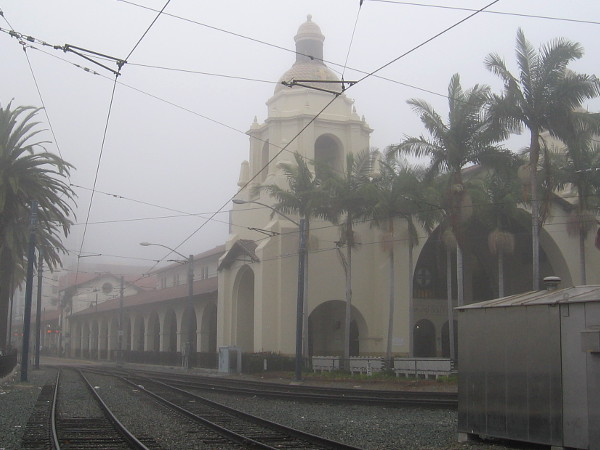 Trolley tracks lead through a fog past Santa Fe Depot in San Diego.