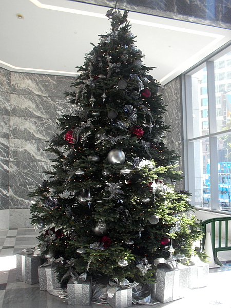 A beautiful, shining Christmas tree in the grand lobby of One America Plaza.