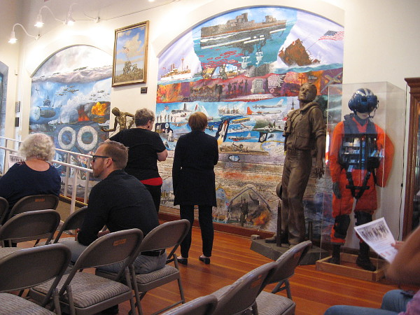 Visitors to the Veterans Museum look at a large mural on one wall before the program begins.