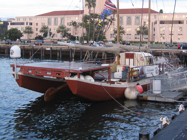 Traditional voyaging canoe Hikianalia docked at the Maritime Museum of San Diego, the County Administration Building in the background.