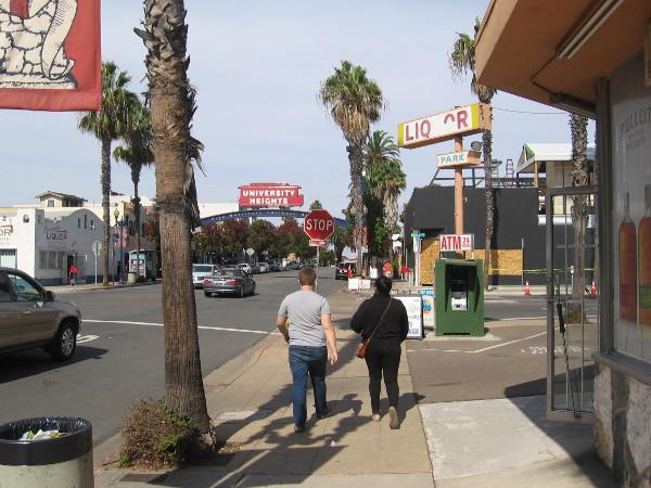 People walk up the Park Boulevard sidewalk toward the University Heights landmark sign.