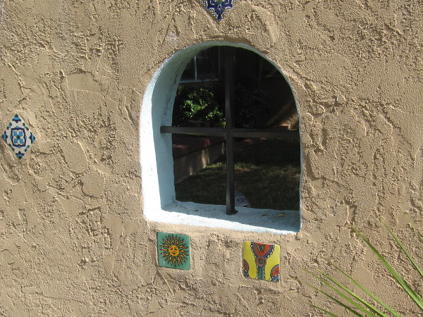 Some small colorful tiles in a stucco wall.