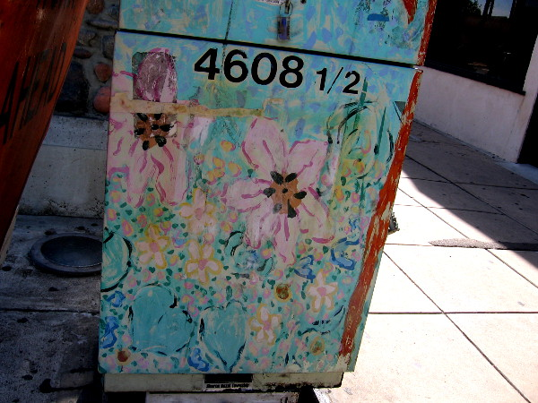 Faded flowery street art on a utility box.