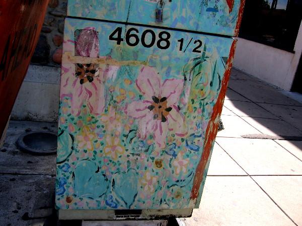 Faded flowery street art on a utility box.