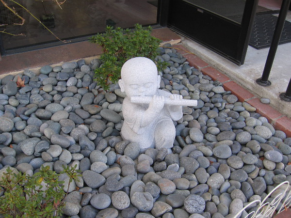 A small, peaceful sculpture in front of Buddha's Light Bookstore.