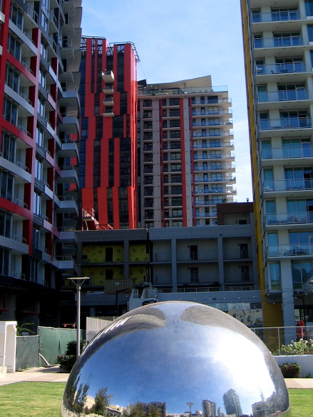 Colorful new residential high-rises beyond one of the two silvery spheres at Fault Line Park in East Village.