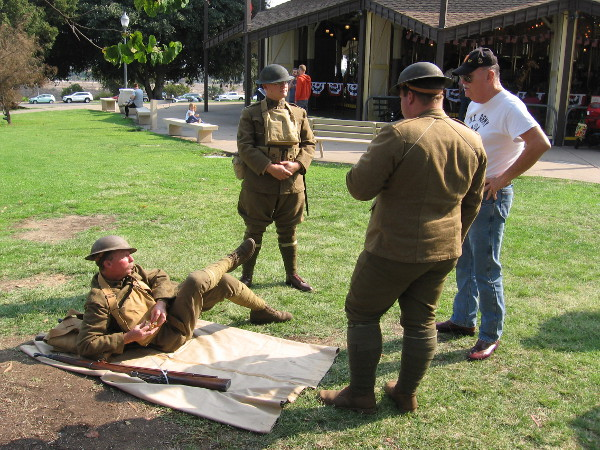 Guys dressed as soldiers hang out on the grass by the Balboa Park Carousel, which itself is over a hundred years old.