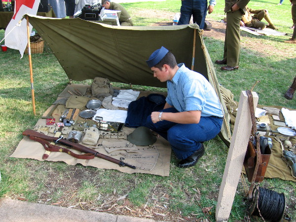 A rifle, canteen, helmet, and other equipment from the battlefield displayed on a blanket.