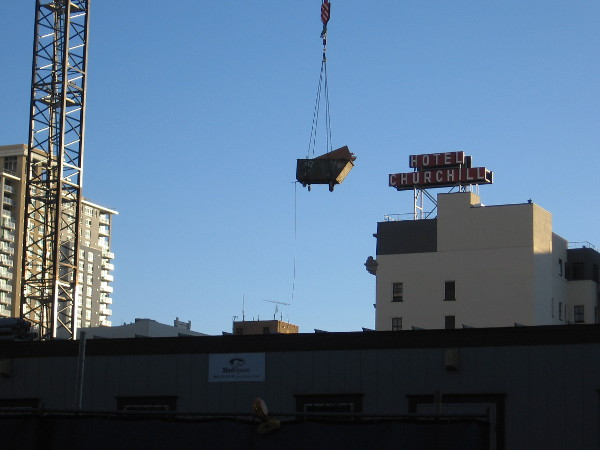 Crane swings a load above the Bosa Tower construction site, with the old Hotel Churchill sign in the background.