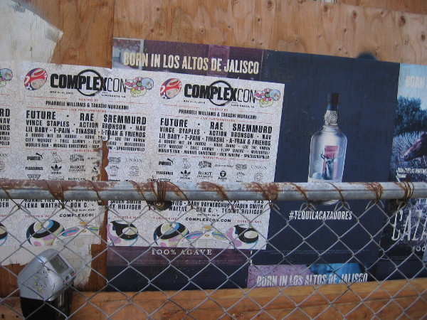 Advertisements peeling from a construction site fence.