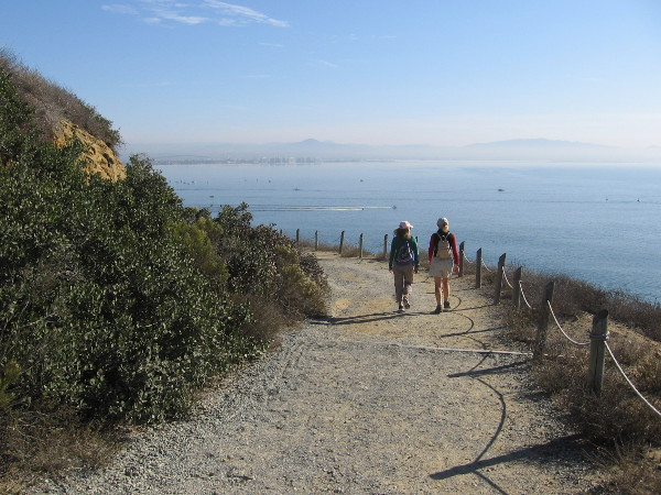 People walk down Cabrillo National Monument's Bayside Trail in order to watch a bit of sailing history.