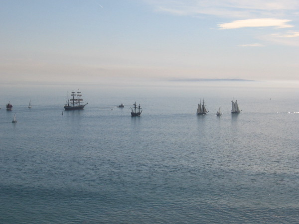 Five amazing tall ships together on the peaceful Pacific Ocean.