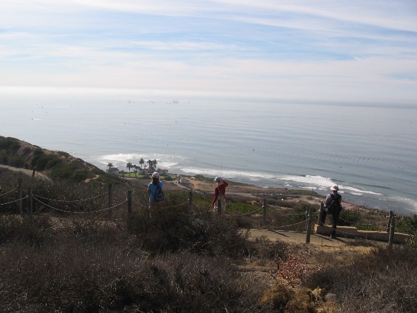 People just below the whale watching overlook of Cabrillo National Monument watch the ships. They gaze past the New Point Loma Lighthouse down by the water's edge.